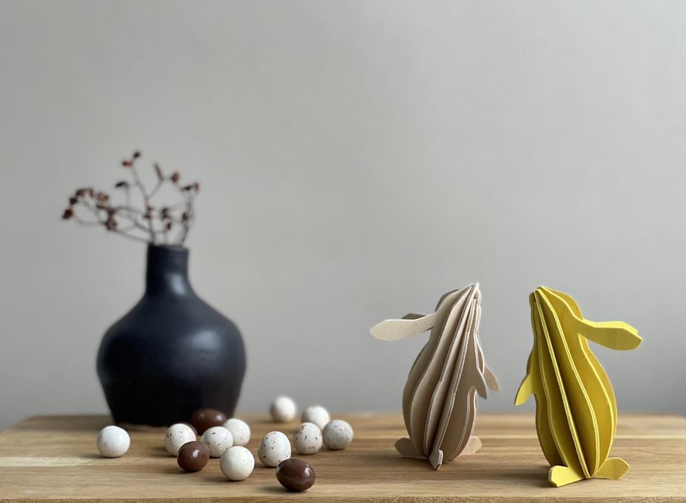 Lovi Rabbits, wooden 3D figures, natural wood and yellow with a vase.