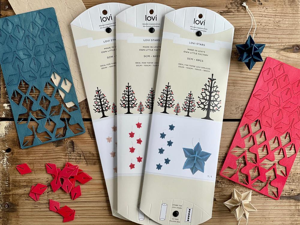 Joulukuusenkoristeet muovittomissa pakkauksissa. Lovi-tähtien monipakkaukset kolmessa värissä: puunvärinen, kirkkaanpunainen ja tummansininen.