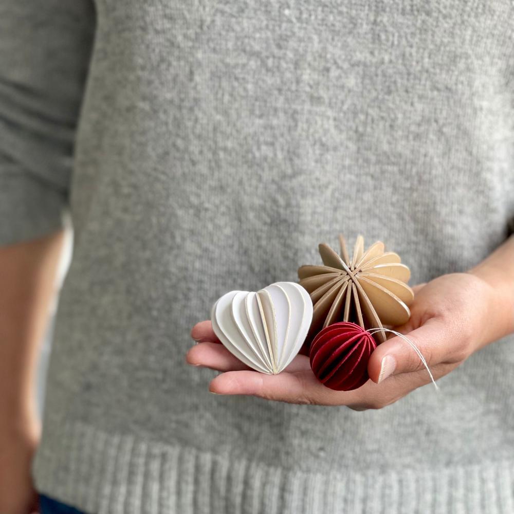 Joulukuusenkoristeet Annen kädessä. Lovi-sydämen ja Lovi-pallon prototyypit